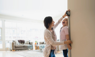 Mother measures child's height and marks door frame.